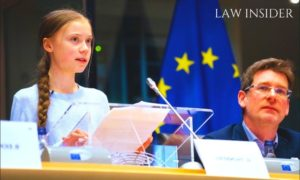 Greta Thunberg alongside a man giving a speech at a conference, wearing a blue Top, a blue colored flag in the background