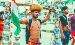 A boy on Kanwar yatra, shirtless in day light wearing a turbun, carrying a black bag, has a wooden stick on his head with steel pots along with them