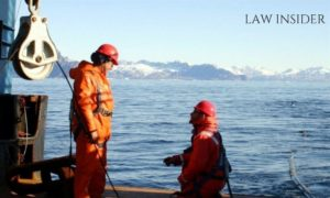 two seafarers in a ship in International waters, working, in their orange uniform.