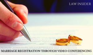 Marriage registration on video call, white form filled by the man with a pen, two golden wedding bands