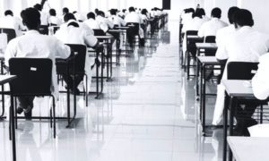 Students giving their NEET Exam in a centre wearing their lab coats and daylight